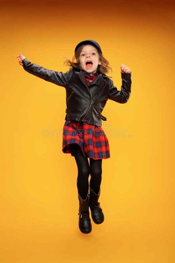 Jumping girl in fashionable clothes. Excited fashionable young girl in stylish clothes jumping on yellow background royalty free stock photo