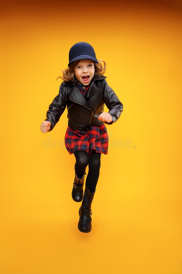Jumping girl in fashionable clothes. Excited fashionable young girl in stylish clothes jumping on yellow background stock image
