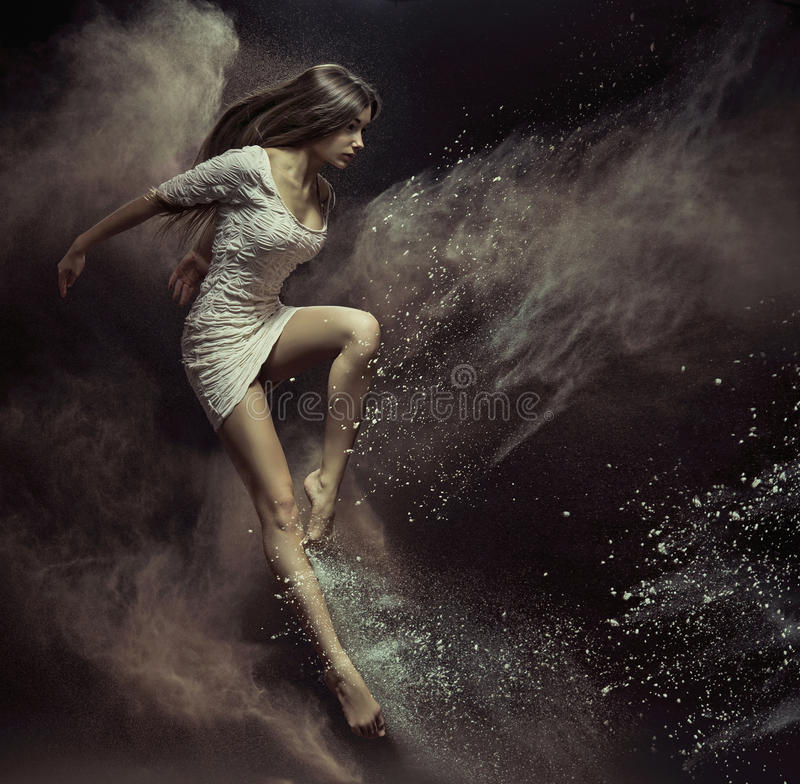 Jumping girl in full of dust place stock image