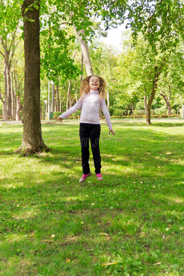 Jumping girl in summer. Photo of cute jumping girl in summer stock photo