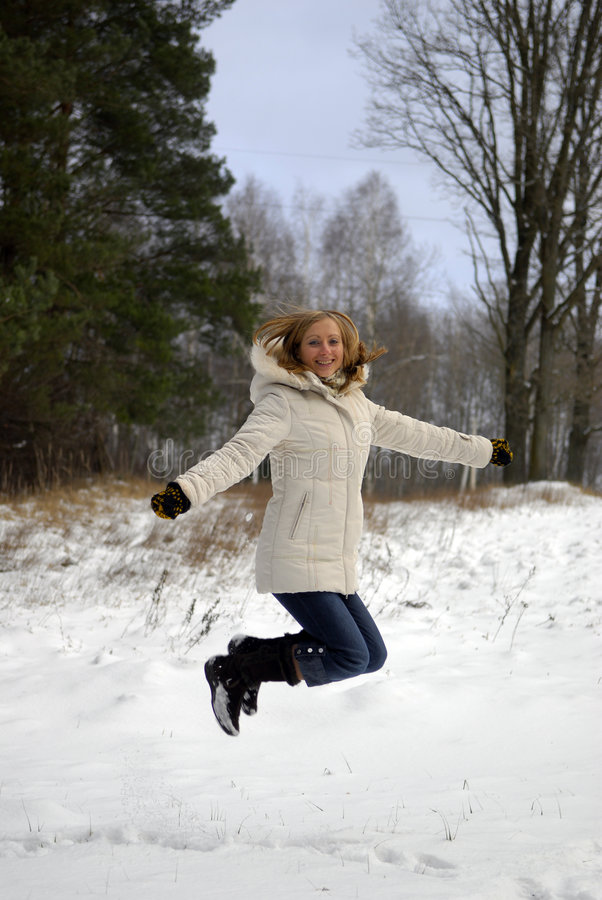Jumping girl wearing winter coat royalty free stock photos