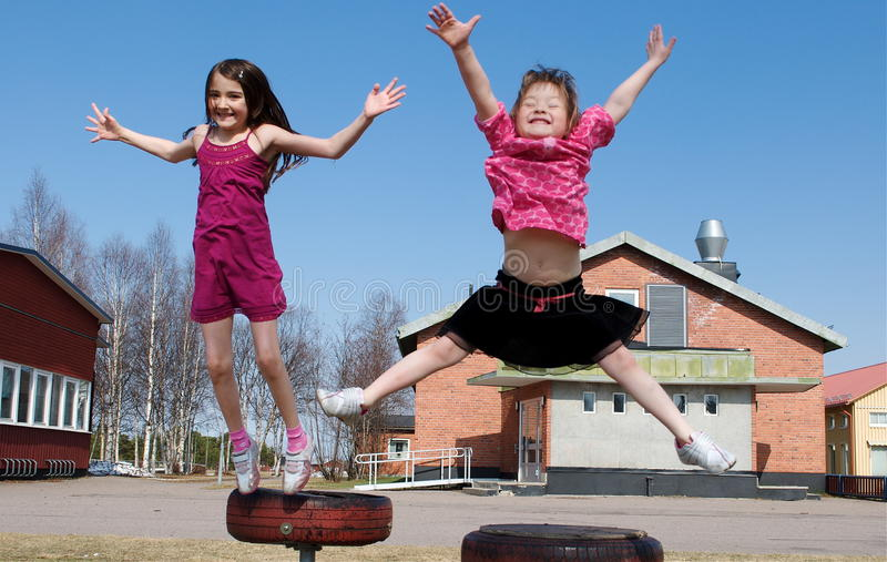 Jumping girls. Happy jumping girls on a blue sky background royalty free stock photos