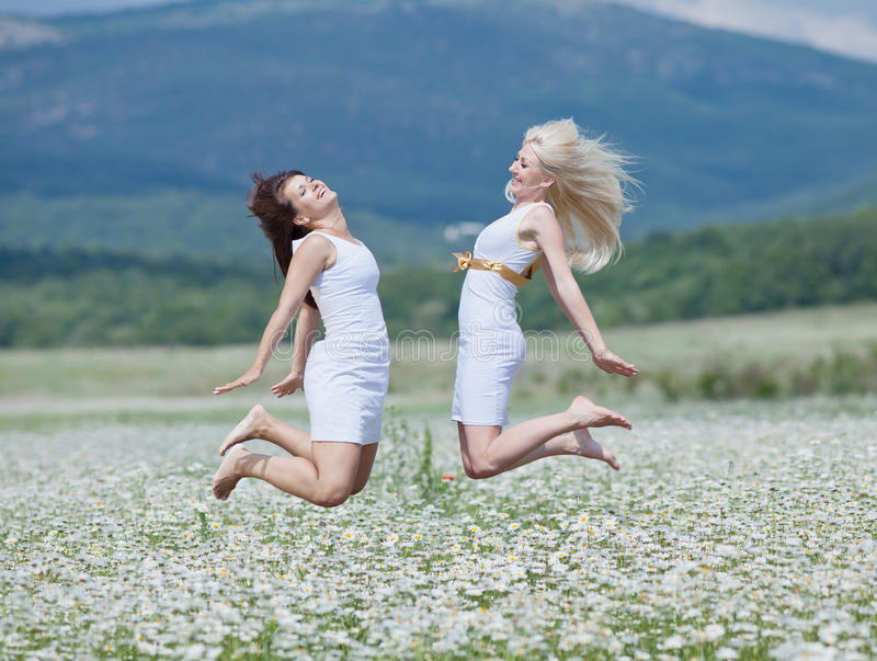 Jumping girls. Attractive young women jumping high in chamomile field royalty free stock photo