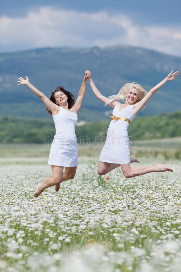 Jumping girls. Attractive young women jumping in chamomile field with raised hands royalty free stock images
