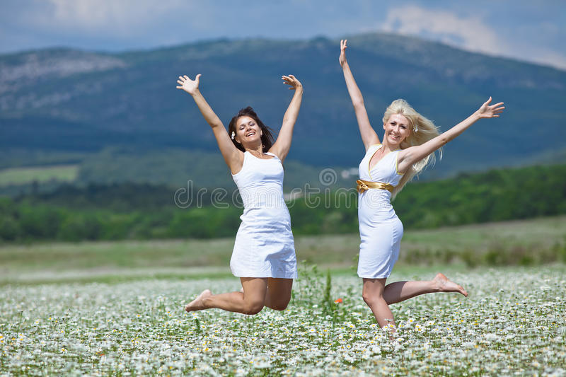 Jumping girls. Attractive young women jumping in chamomile field with raised hands. Jumping girls royalty free stock photos