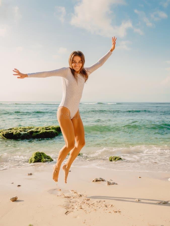 Jumping glückliche Frau in Badeanzug am Meeresstrand bei Sonnenuntergang Sommerferien stockbilder