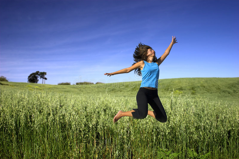 Jumping on a green field stock images