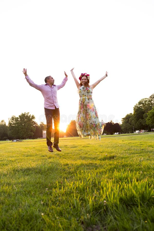 Jumping happy couple on green field in summer park royalty free stock photos