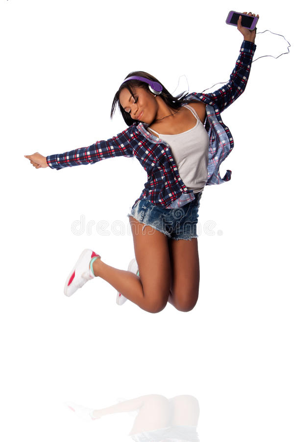 Jumping happy dancing listening to music. Beautiful happy teenager jumping dancing jamming listening to music, on white stock photo