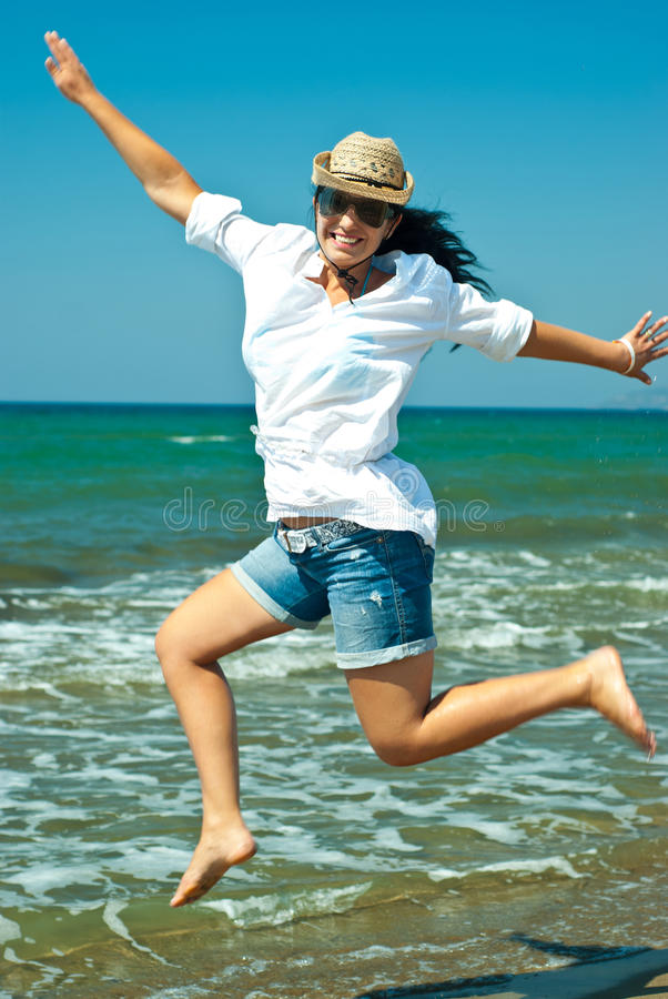 Jumping happy woman on the beach royalty free stock images