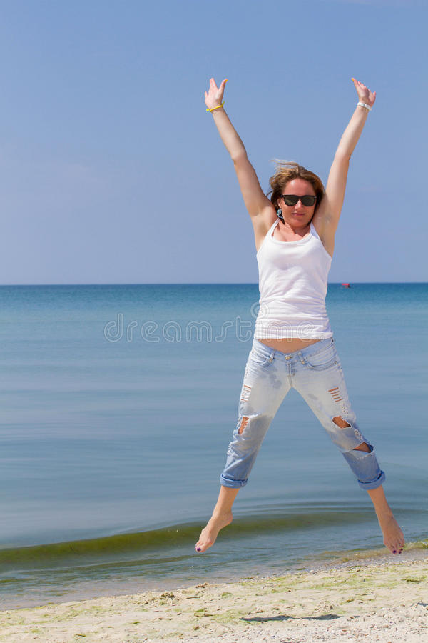Jumping happy woman on the beach, fit sporty healthy body in blue jeans, woman enjoys wind, freedom, vacation stock photos
