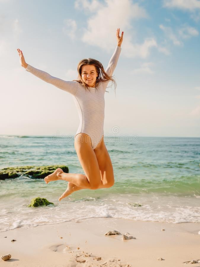 Jumping happy woman in swimsuit on ocean beach at sunset. Summer holidays stock photography