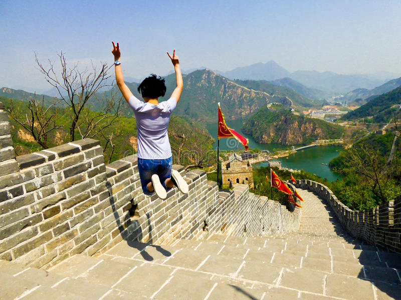 Jumping on Huanghuacheng Lakeside Great Wall section. An asian woman jumping on Huanghuacheng Lakeside Great Wall one section stairs on the mountain in Beijing stock image