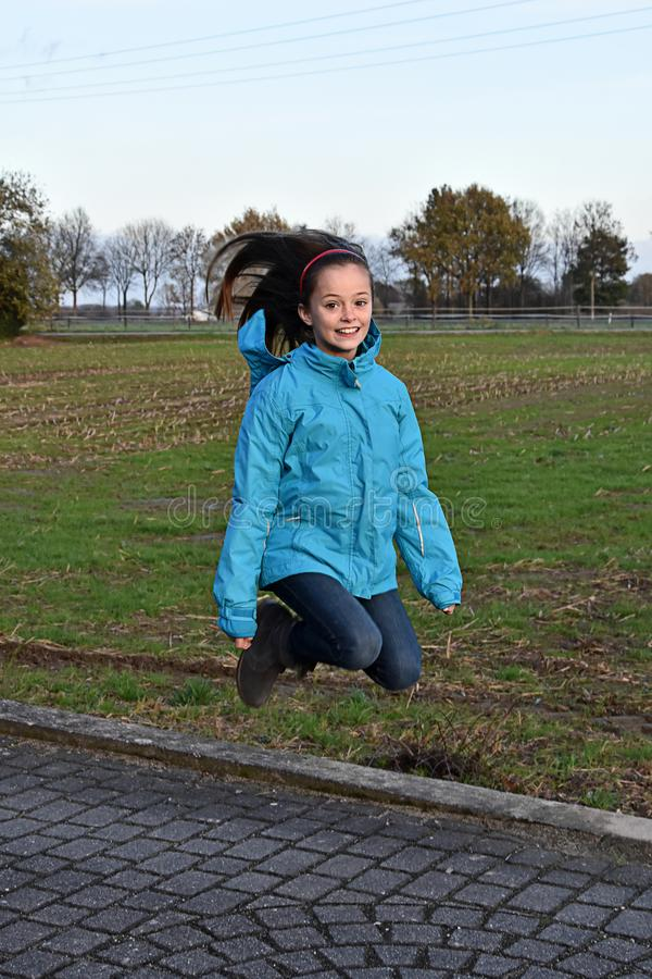 Jumping for joy, happy teenage girl. Sweet teenage girl with waving hair jumps for joy royalty free stock photo