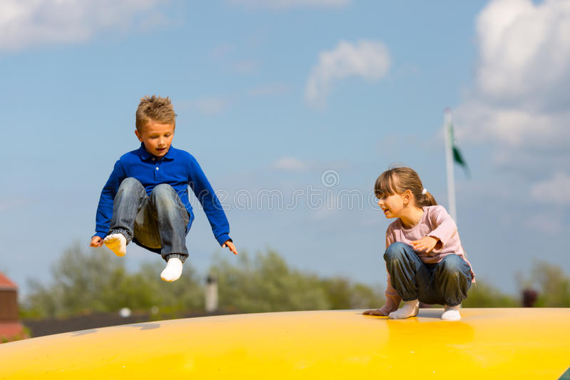 Jumping kids. Kids on bouncy cushion. Trademarks have been removed royalty free stock images