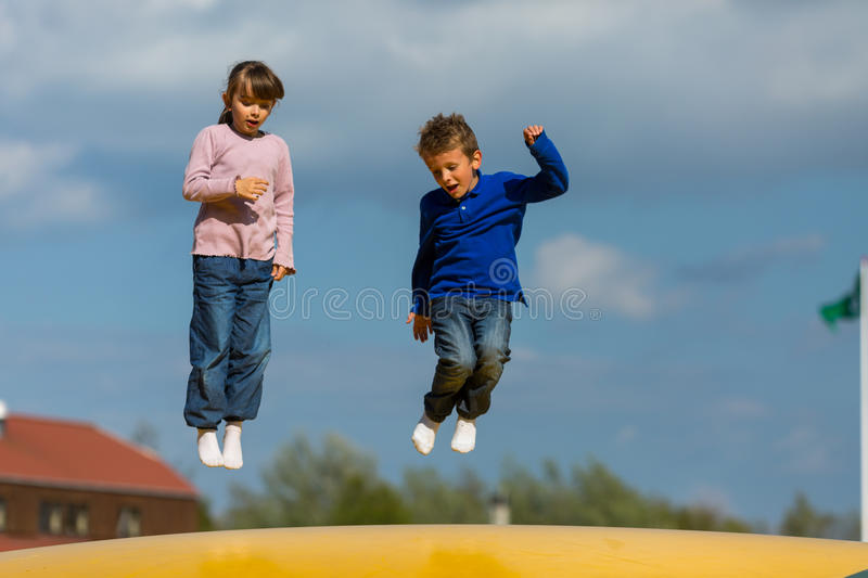 Jumping kids. Kids having fun on bouncy cushion. Trademarks have been removed royalty free stock photos