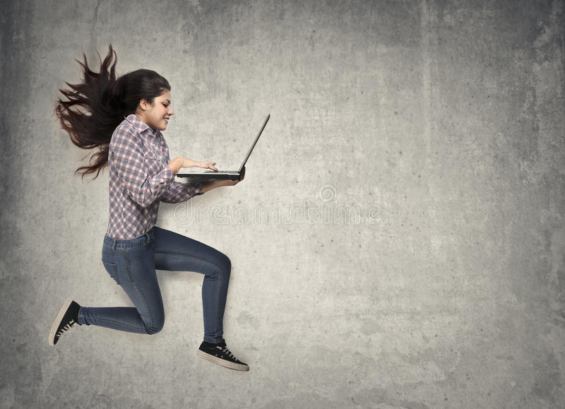 Jumping with laptop stock photography