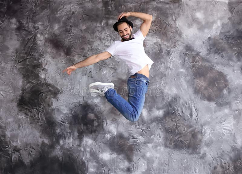 Jumping male dancer against grunge wall royalty free stock images