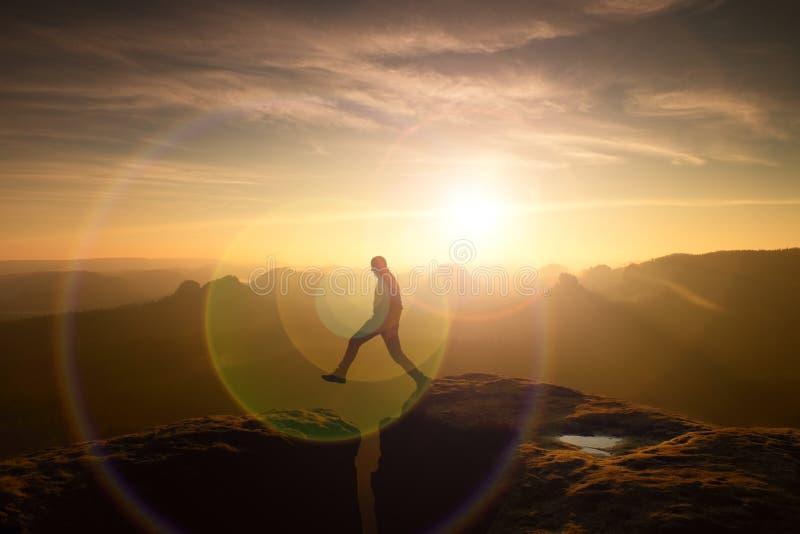 Jumping man. Young man makes step between cliffs. stock photo