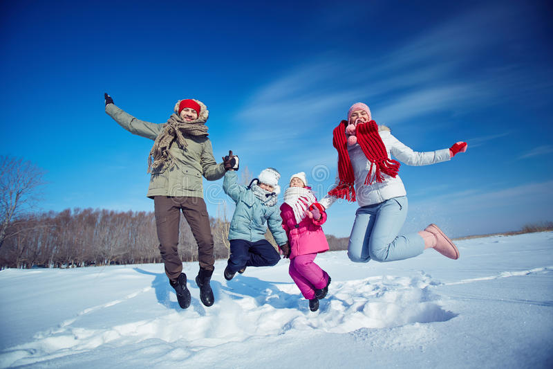 Jumping over snowdrift. Ecstatic family of four jumping in snow stock photography
