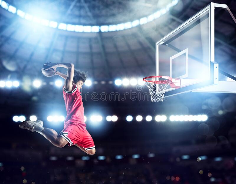 Jumping Player throws the ball in the basket in the stadium full of spectators stock photo