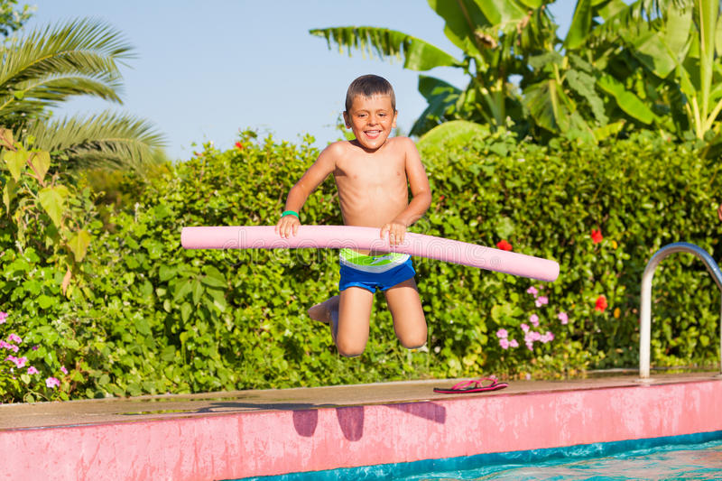 Jumping in pool small boy holding inflatable ring. Jumping small boy holding inflatable ring standing near the swimming pool outside in summer stock photography