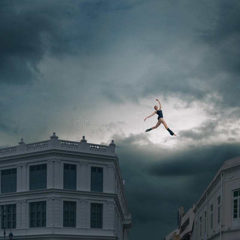 Jumping between roofs. Abstract design of ballet dancer jumping between roofs royalty free stock image