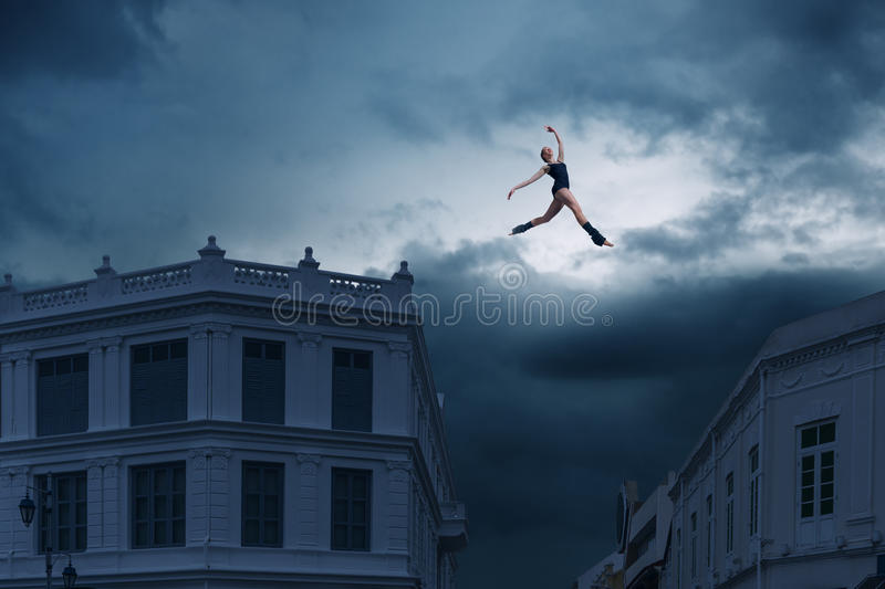 Jumping between roofs. Abstract design of ballet dancer jumping between roofs stock photos