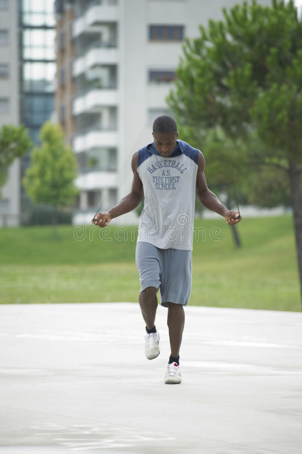 Jumping Rope. Young man jumping rope outdoors royalty free stock photography