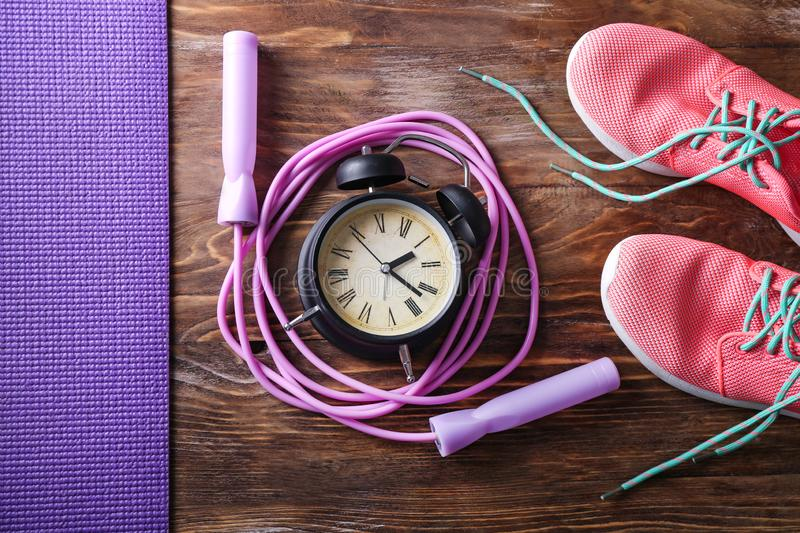 Jumping rope with alarm clock and sport shoes on wooden background royalty free stock photography