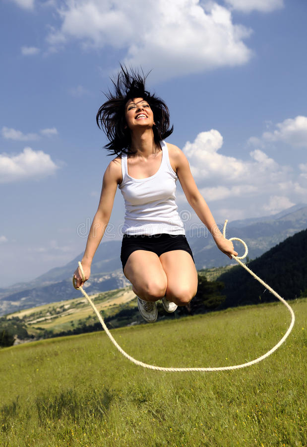 Jumping rope attractive women in meadow stock image