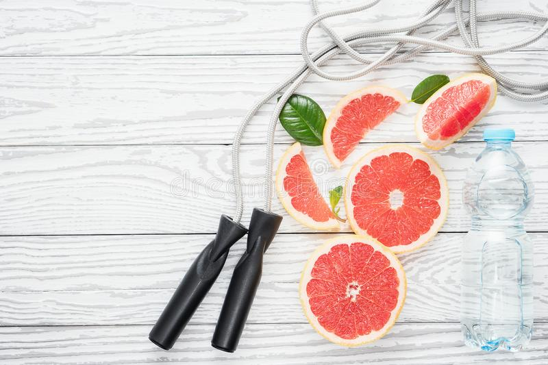 Jumping-rope, fresh grapefruits and bottle of water, on rustic white wooden table , top view, flat lay, fitness accessories. royalty free stock image