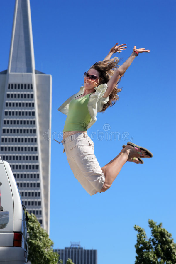 Jumping in San Francisco. Young woman jumping in downtown San Francisco royalty free stock images