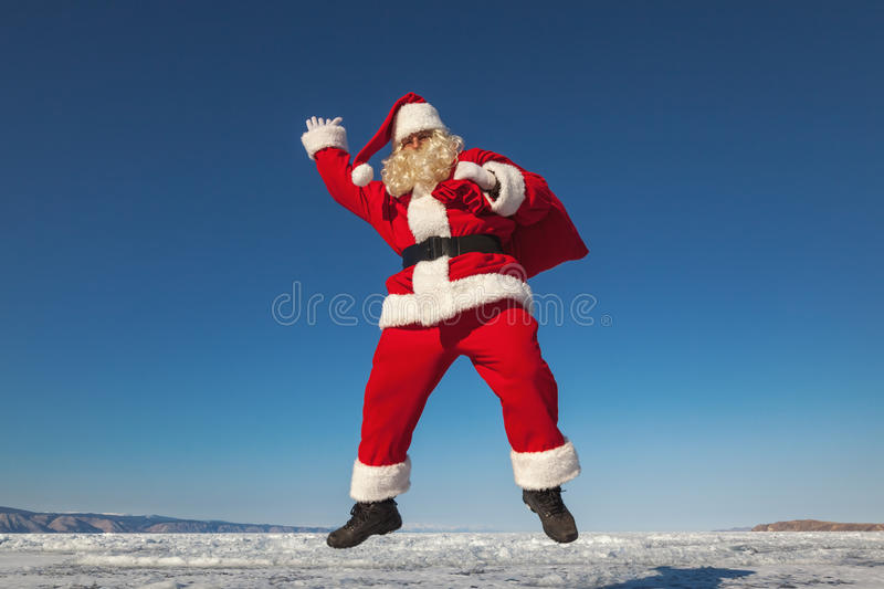 Jumping Santa Claus outdoors. Santa Claus joyously jumping in the snow, shooting was conducted in a sunny day on lake Baikal royalty free stock images