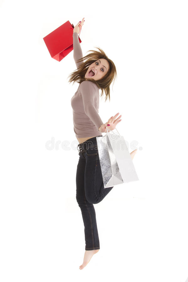 Jumping shopper woman. Happy shopper woman jumping with bags isolated on white stock image