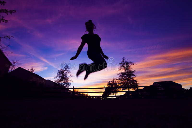 Jumping silhouette. A silhouette of a girl jumping into the air against a purple sky royalty free stock image