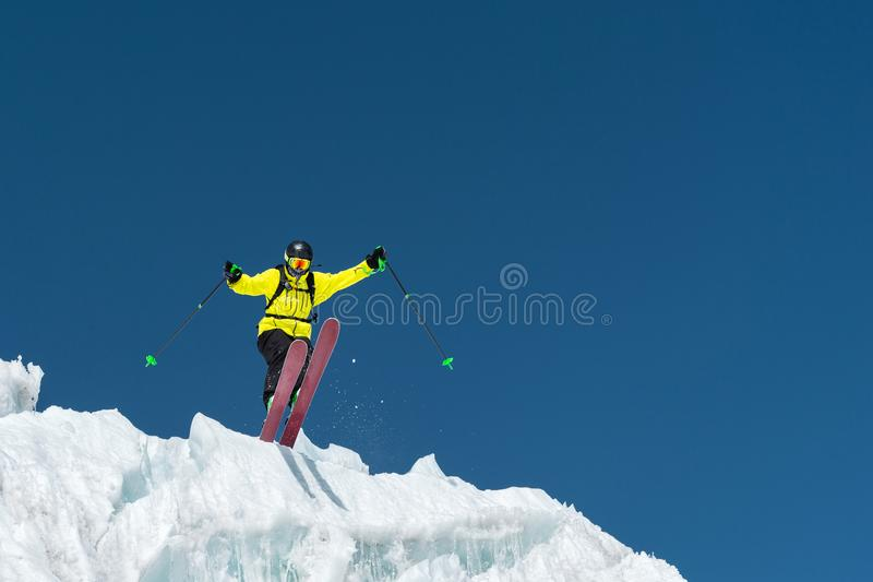 A jumping skier jumping from a glacier against a blue sky high in the mountains. Professional skiing.  royalty free stock images