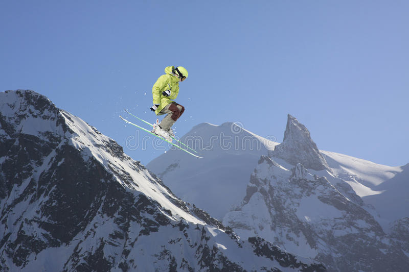 Jumping skier in mountains. Extreme sport, freeride. Jumping skier in winter snowy mountains. Extreme sport, freeride royalty free stock images