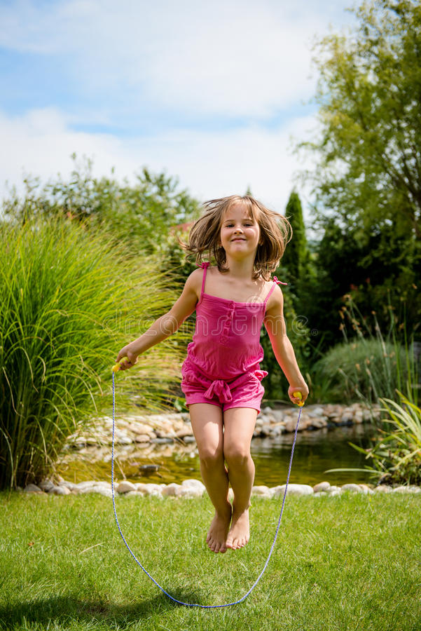 Jumping with skipping rope. Active child - happy girl jumping with skipping rope outdoor in backyard stock images