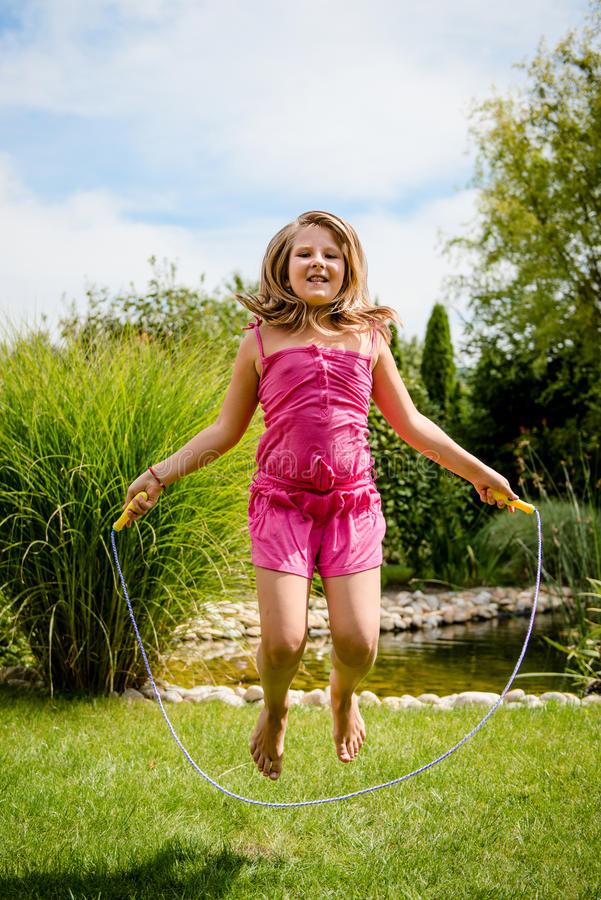 Jumping with skipping rope. Active child - happy girl jumping with skipping rope outdoor in backyard stock photo