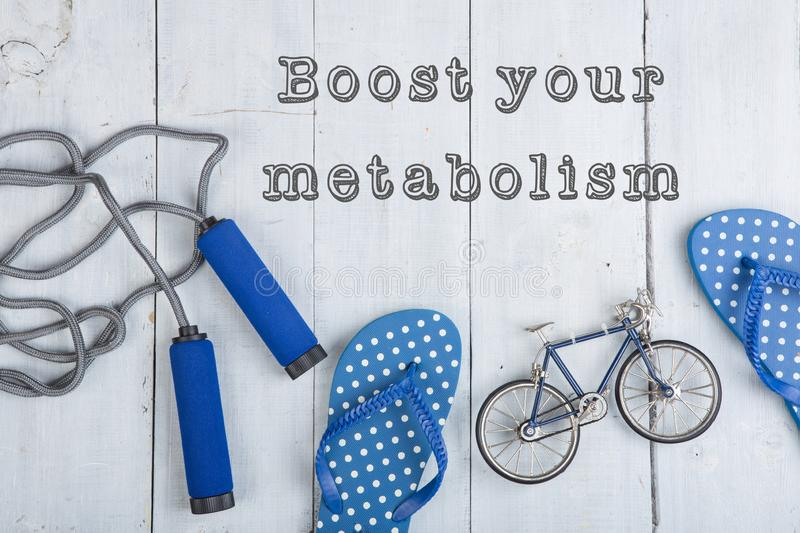 Jumping/skipping rope with blue handles, flip flops, model of bicycle on white wooden background with text boost your metabolism stock image