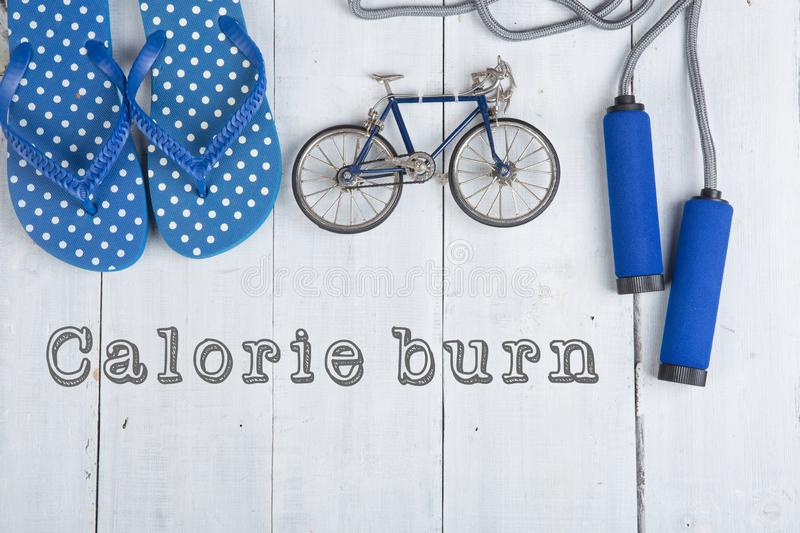 Jumping/skipping rope with blue handles, flip flops, model of bicycle on white wooden background with text calorie burn royalty free stock photo