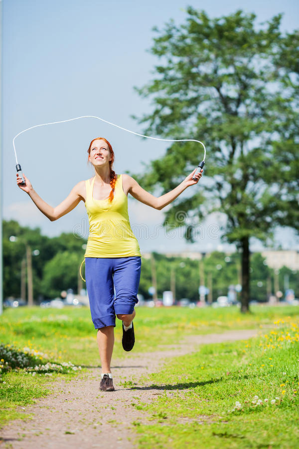Jumping with skipping rope. Young happy redhead woman jumping skipping rope stock image
