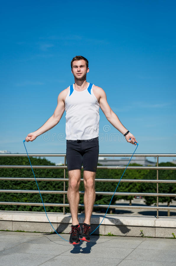 Jumping with skipping rope. Young sport man exercising - jumping with skipping rope royalty free stock photography