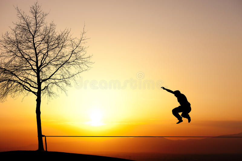 Jumping on slackline. Silhouette of teenager jumping on slackline royalty free stock photos