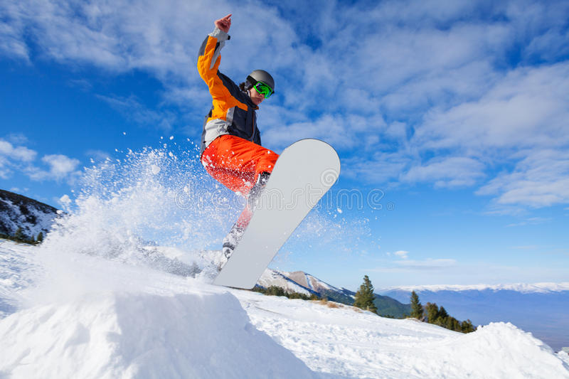 Jumping snowboarder from hill in winter royalty free stock image