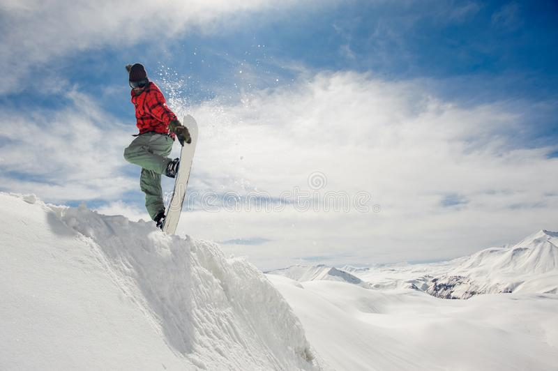 Jumping snowboarder keeping hand on the snowboard on blue sky background stock images