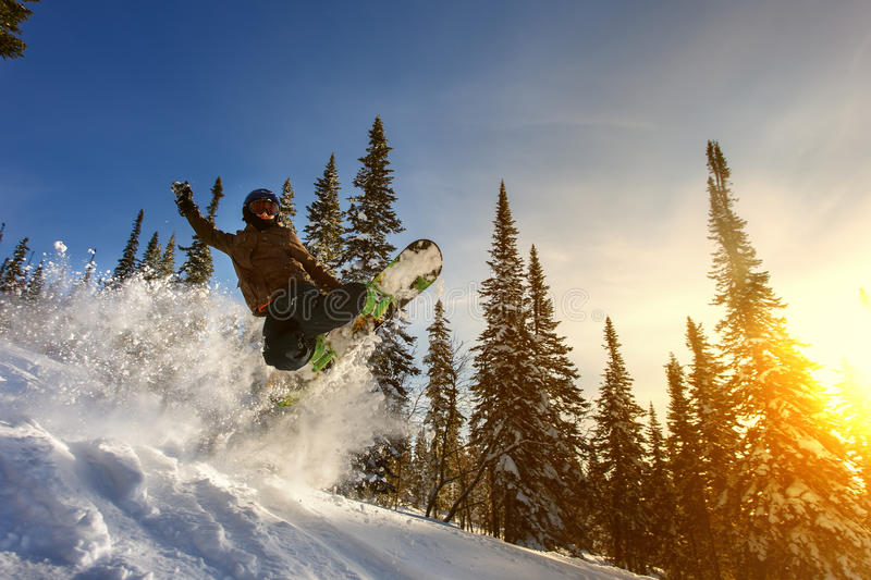 Jumping snowboarder on snowboard in mountains in ski resort royalty free stock photos