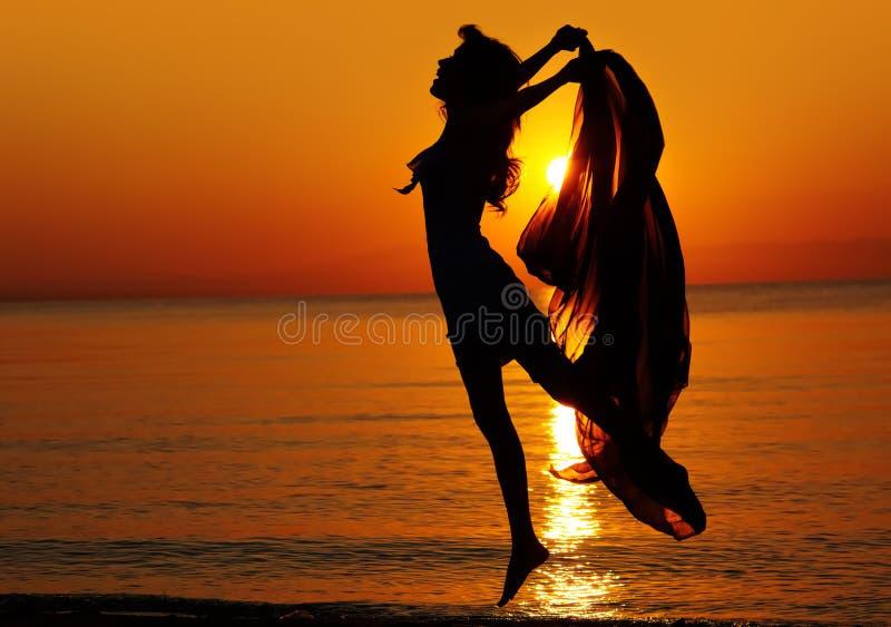 Jumping at sunset royalty free stock image