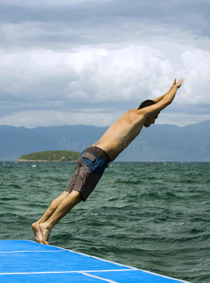 Jumping to sea. A young cute man is jumping to sea royalty free stock photos